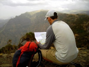 Trauma checks map and compass heading as he hikes across Africa.