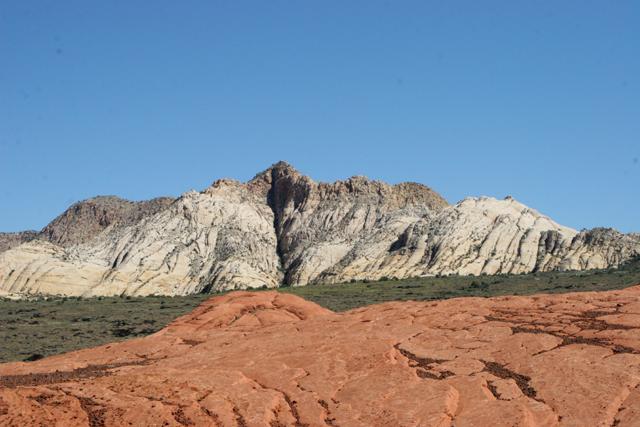 White mountains overlook petrified sand dunes.