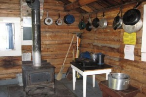 Interior of Hogan Cabin with wood stove and basic cooking hardware.